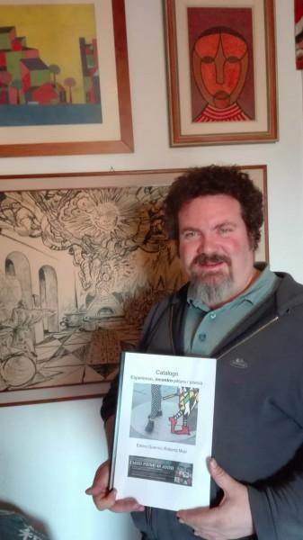 212-enrico-guerrini-nel-suo-laboratorio-con-il-catalogo-di-pittopoesia-incontro-pittura-poesia